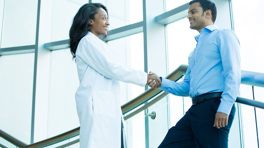 Closeup portrait of health care professional or doctor or nurse shaking hands with patient, indoors clinic hospital background